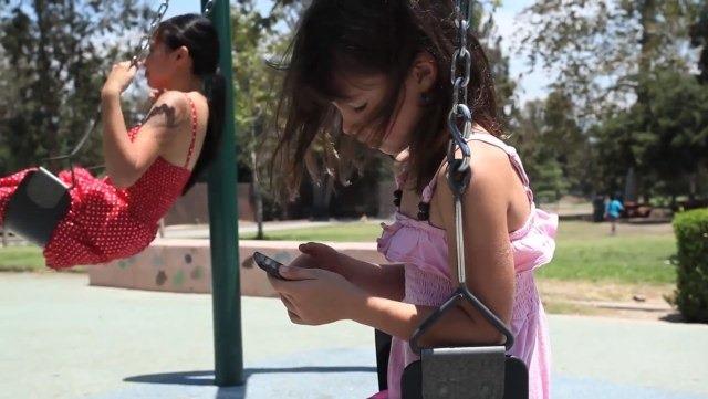 nena-jugando-con-celular-en-hamaca